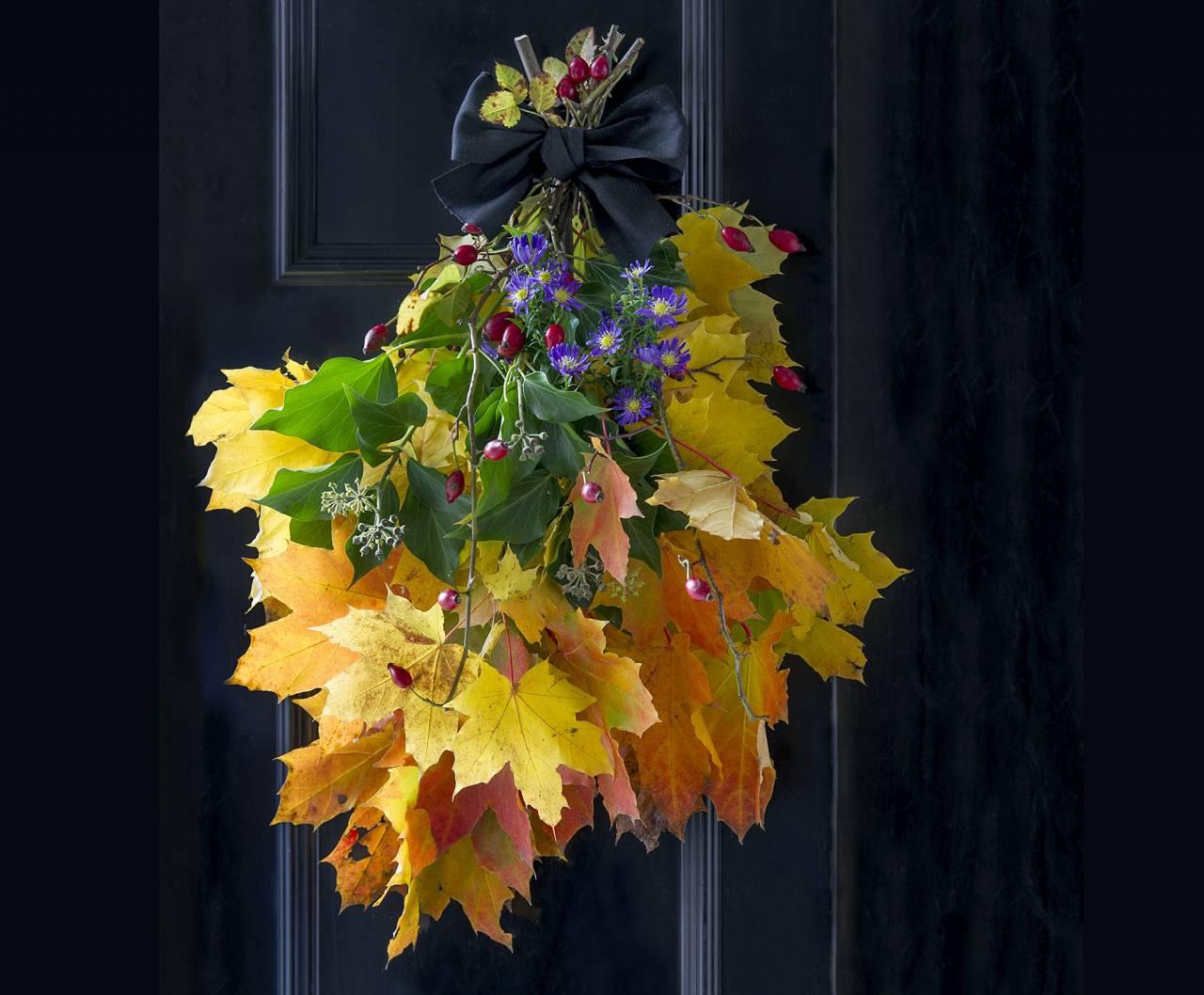 Vacker dörrdekoration av höstlöv.