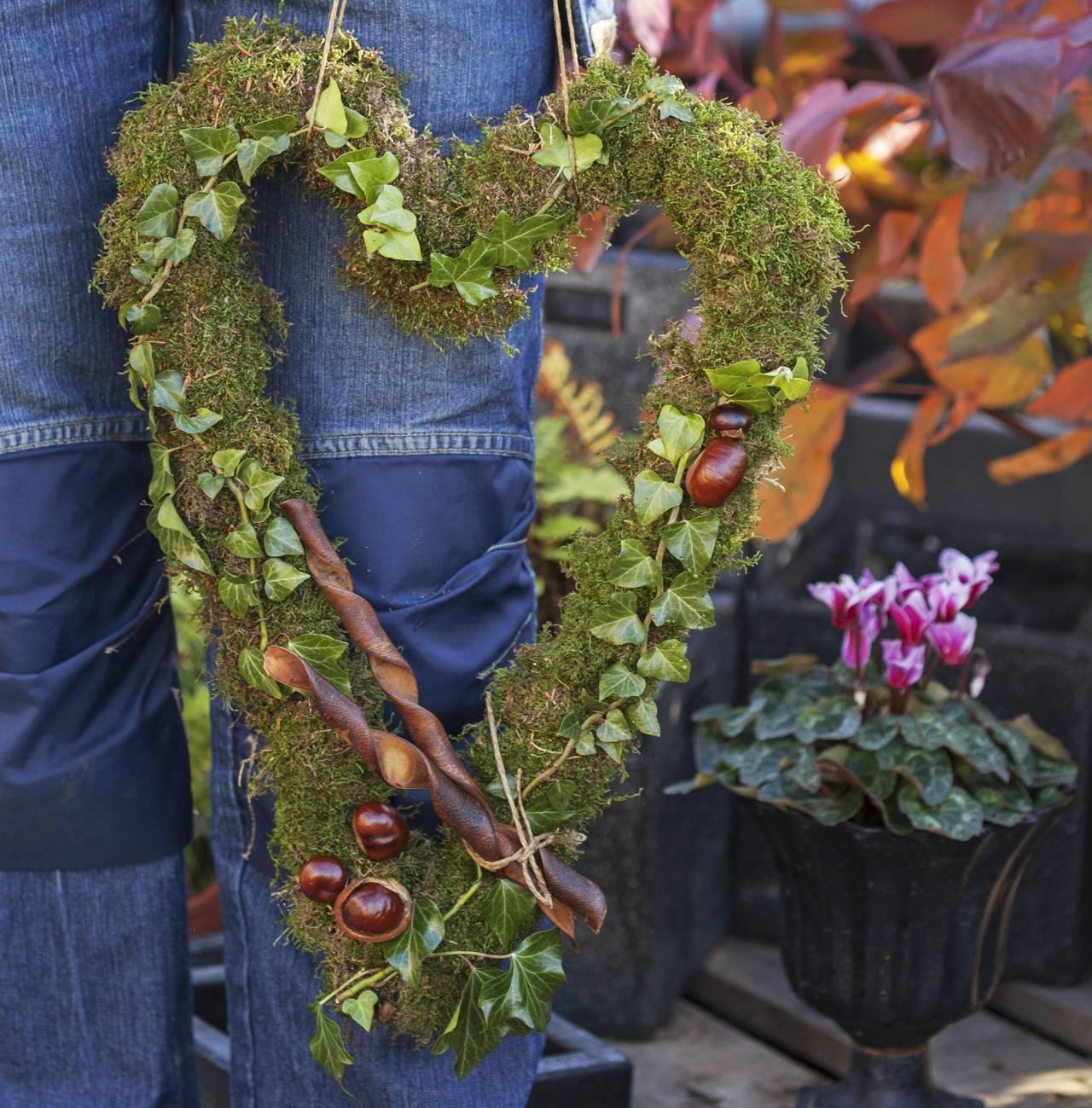 Hjärta av grönt dekorerat med kastanjer och murgröna