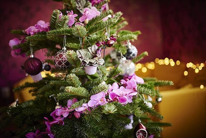 Julgran dekorerad med lila blommor och pynt i matchande färg