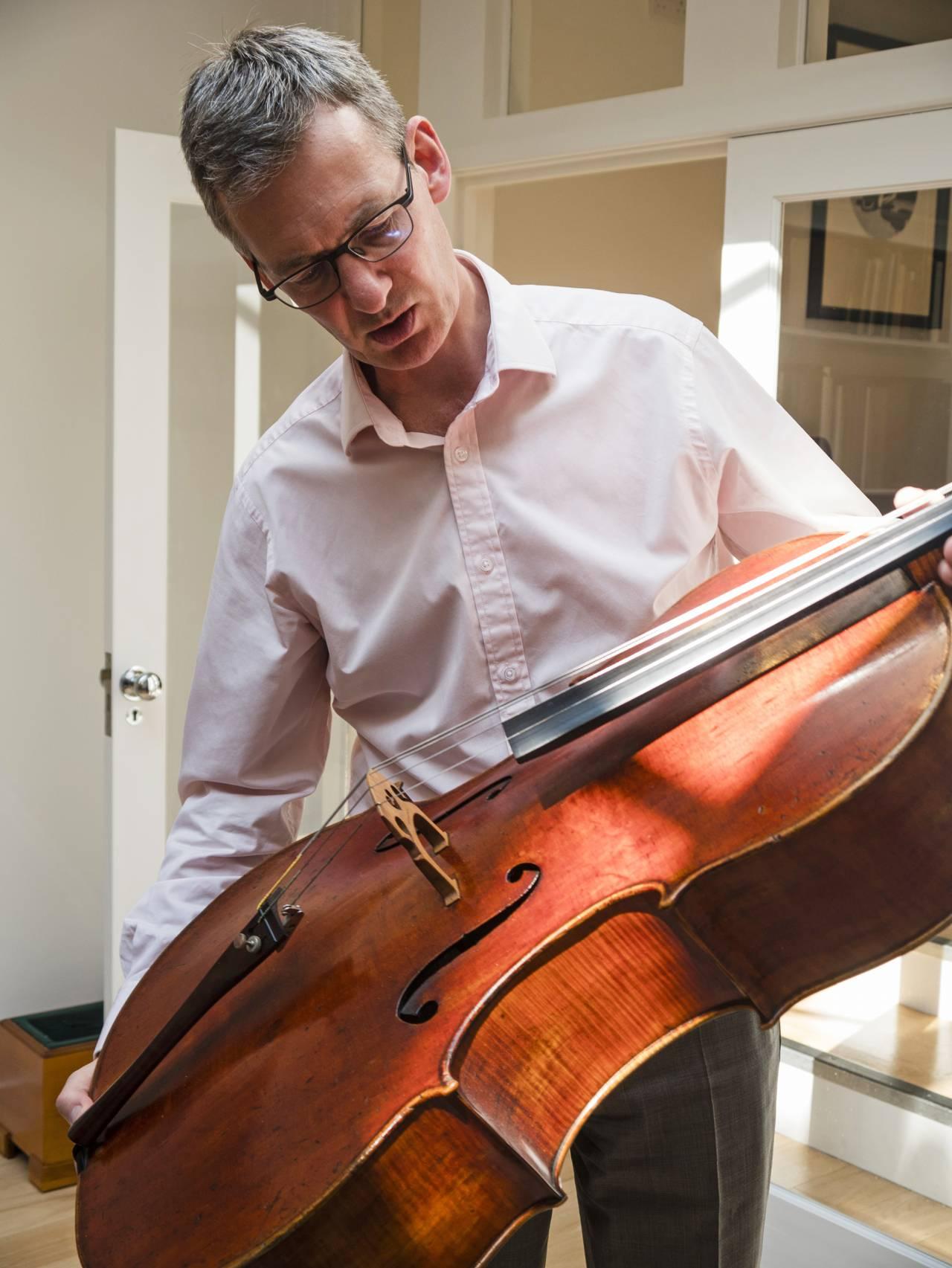 auktionsförrättaren Tim Ingles med ett instrument
