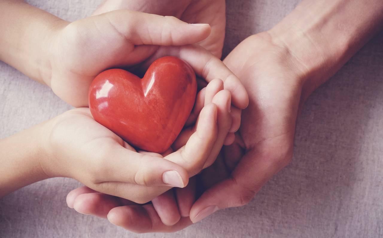 Två par händer håller ett rött hjärta i porslin