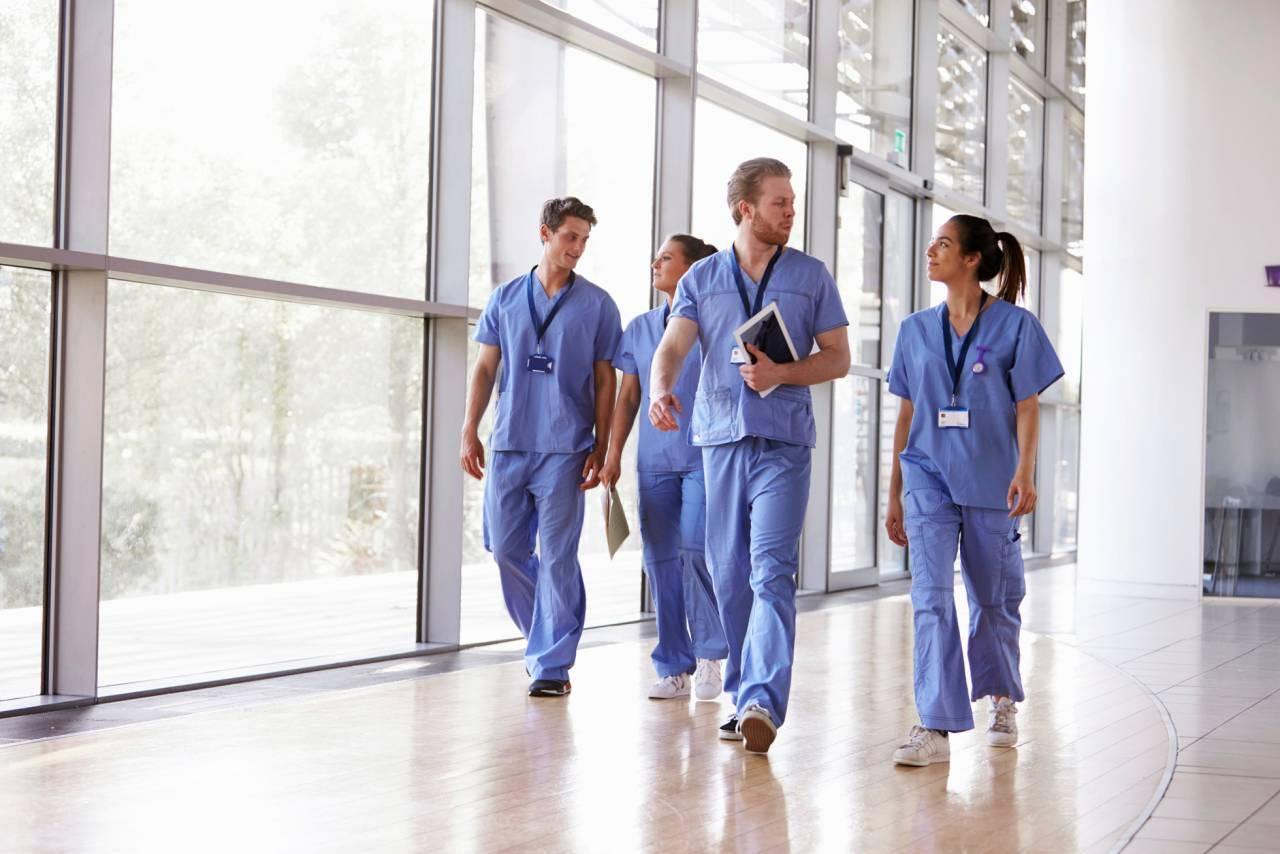 Sjukhuspersonal i grupp pratar med varandra