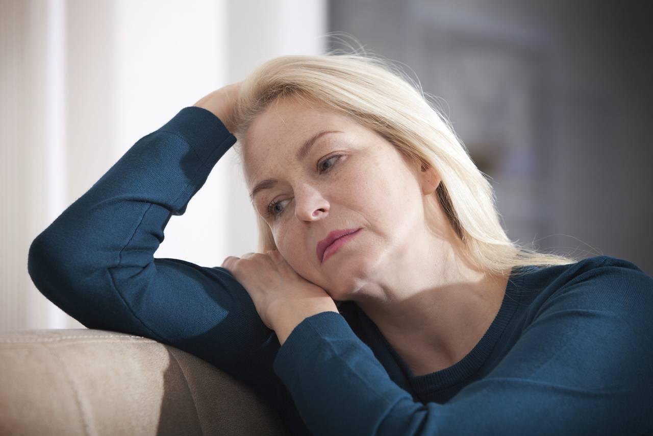 Kvinna ser ledsen ut i en soffa