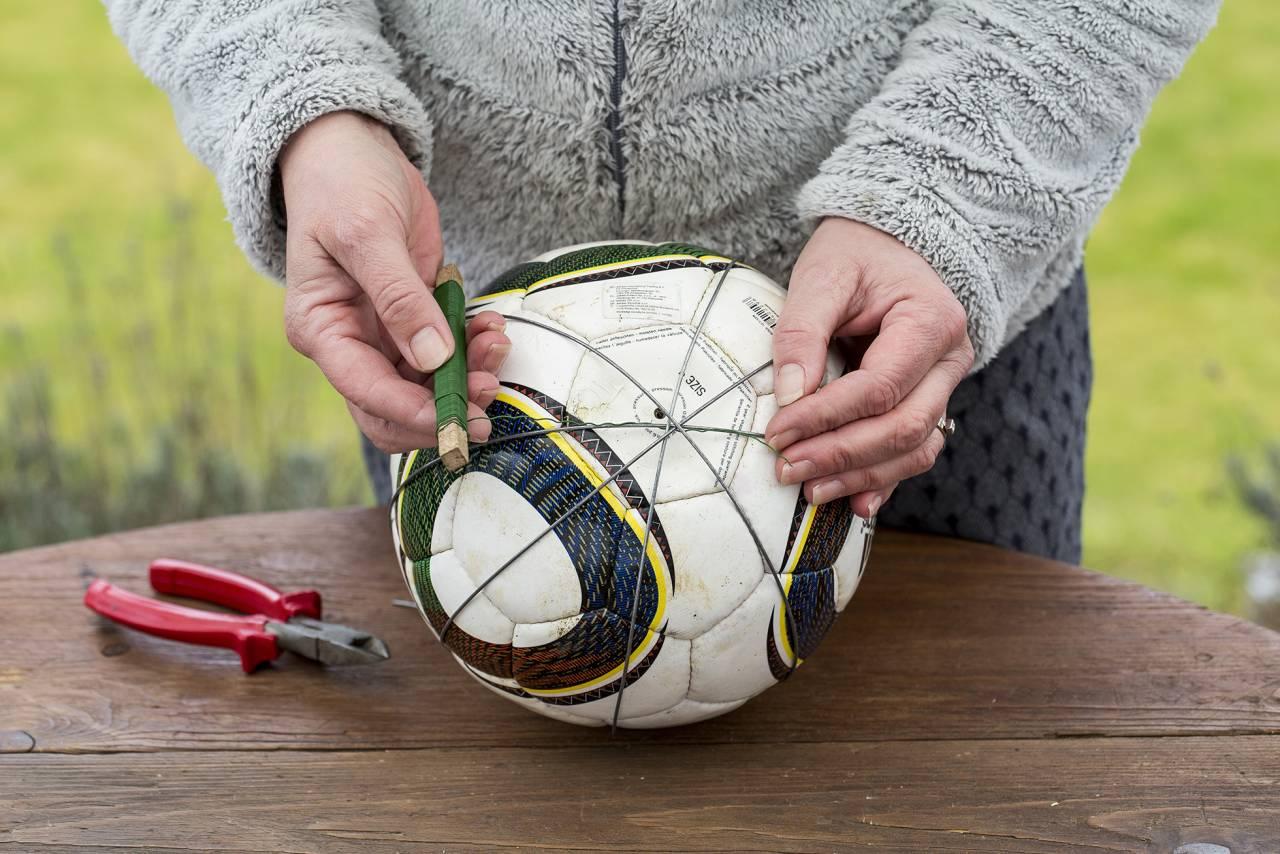 Kvinna visar upp ståltråd, avbitartång och fotboll som ska bli ett hemgjort spaljéklot