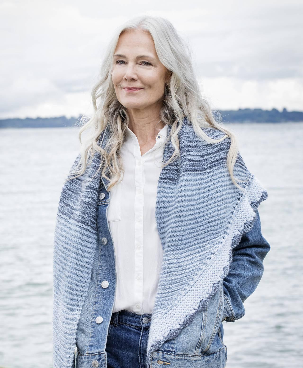 Kvinna tittar ut över havet i rätstickad sjal