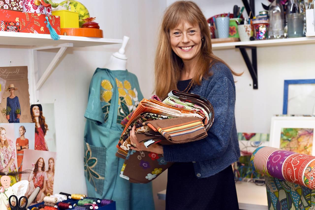Ann-Sofie, som brinner för hållbart mode, står i sin ateljé med tyger i handen.