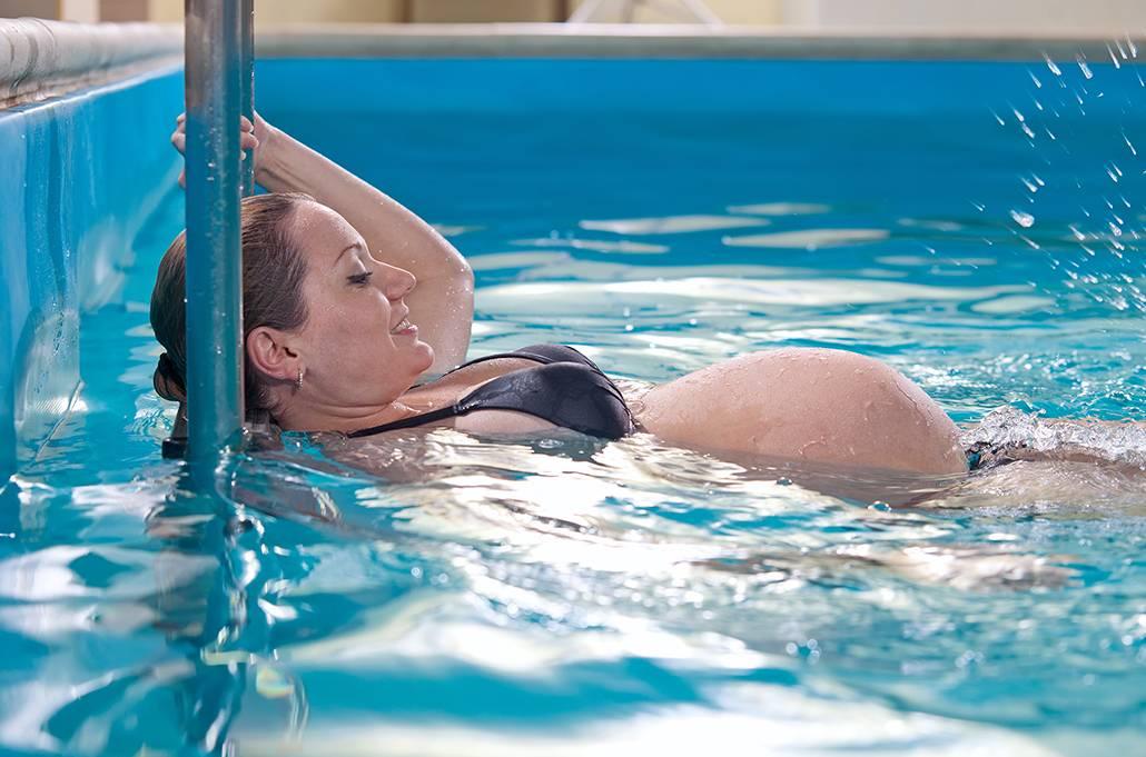 Gravid kvinna gör vattengympa