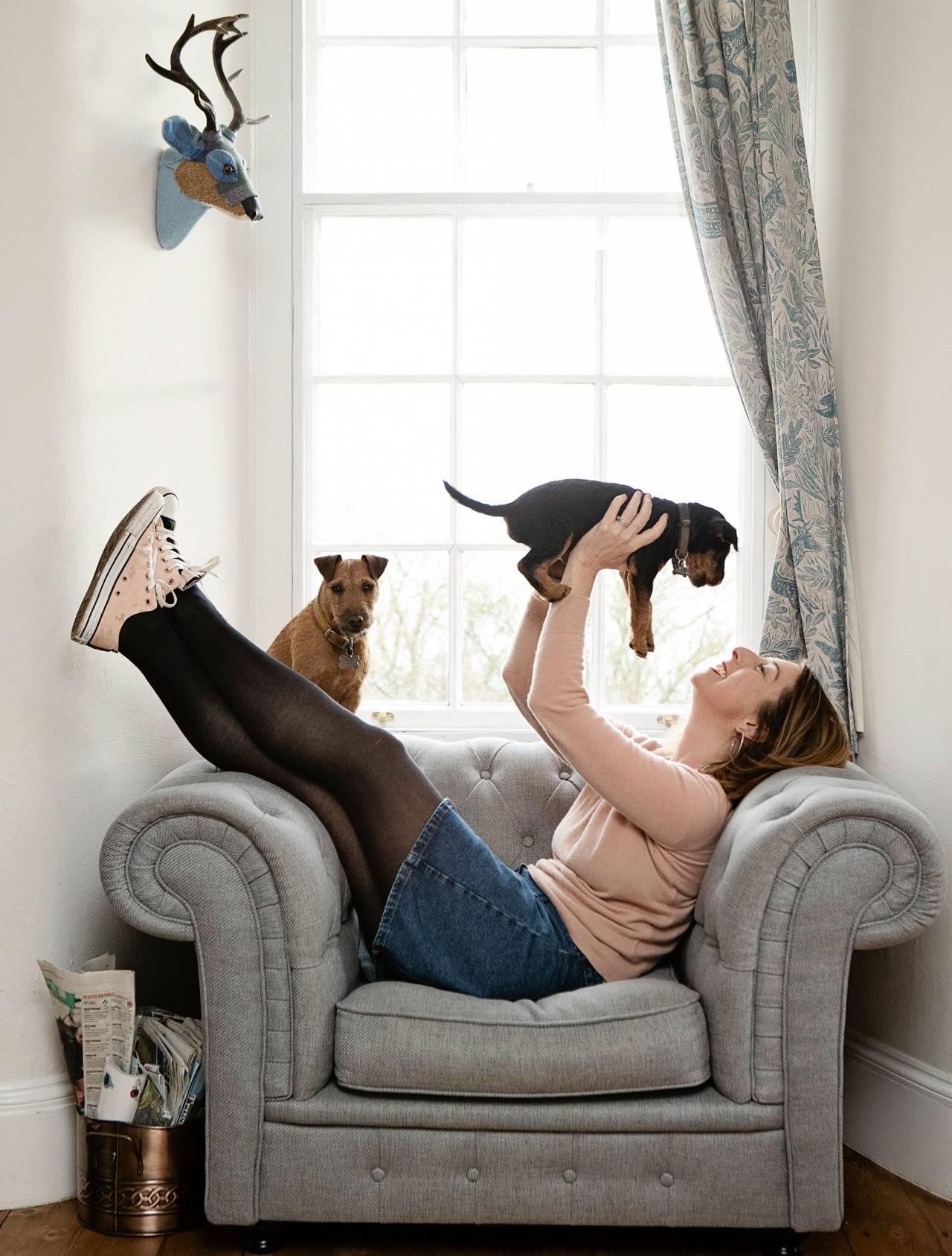 Författaren Jenny Colgan ligger i en fåtölj och myser med sina små hundar.