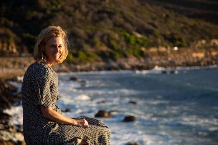 Marie Sammeli sitter vid vattnet i Sydafrika med ett berg i bakgrunden.