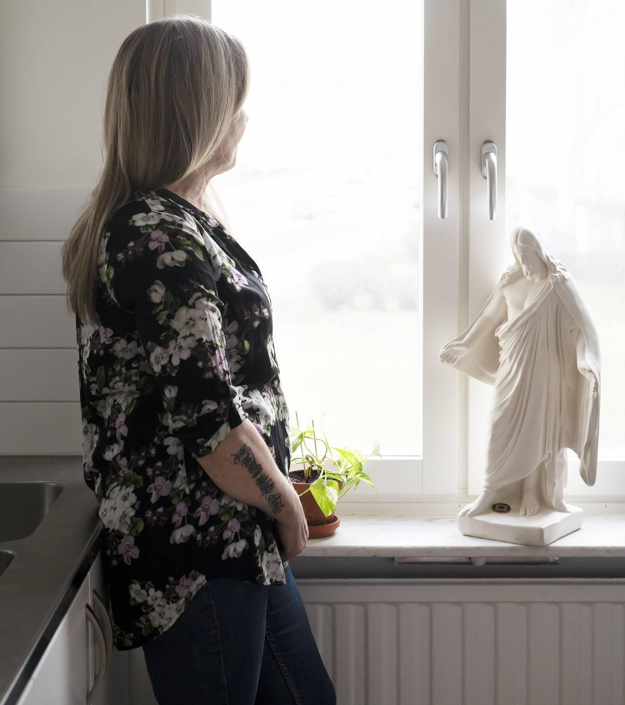 Anne står vid ett fönster och tittar ut. På armen har hon tatuerat in sin döde sons namn.