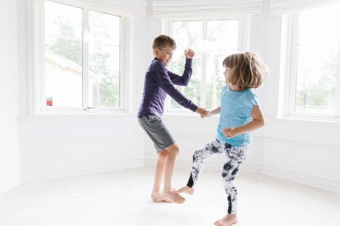 Två barn som tränar balans tillsammans.