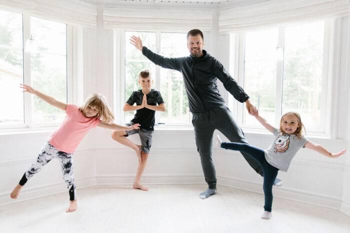 Pappa med tre barn som tränar yoga tillsammans.