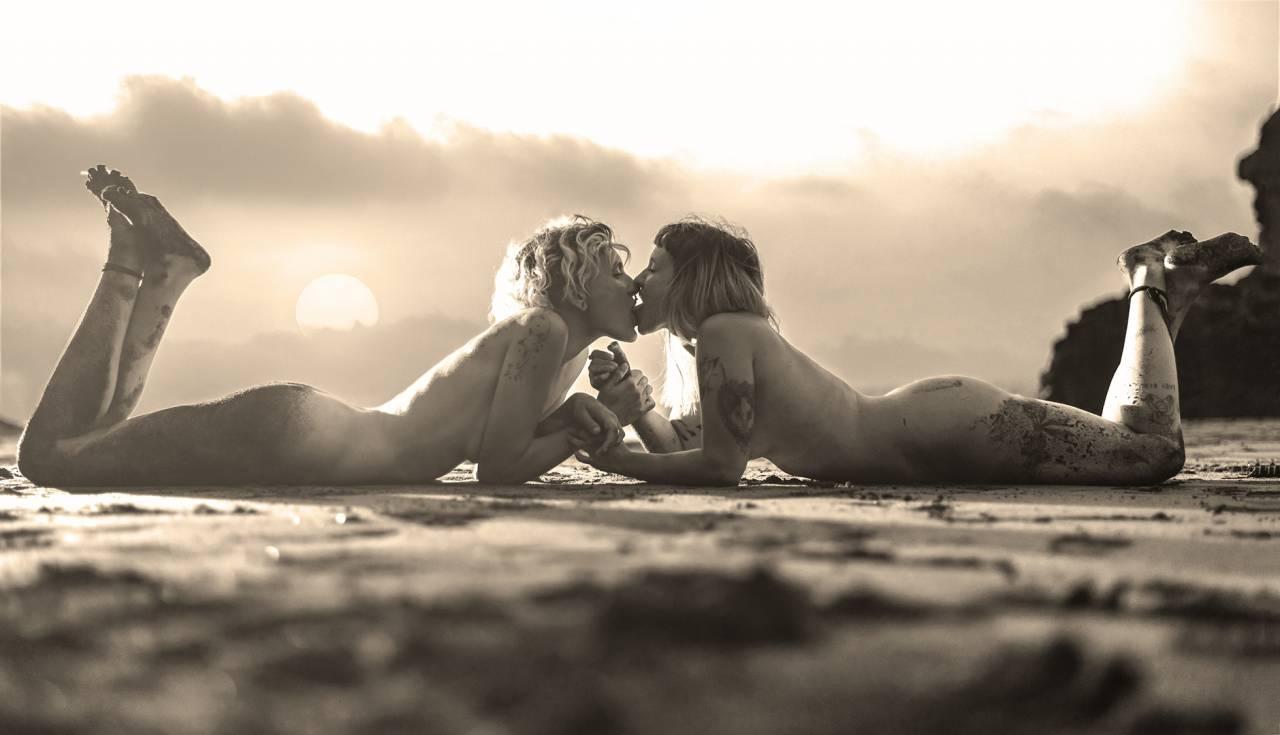 Två kvinnor ligger nakna på marken och tittar varandra i ögonen