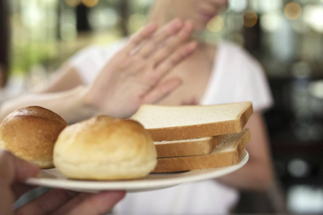 Kvinna tackar nej till glutenfyllda produkter som vitt bröd.