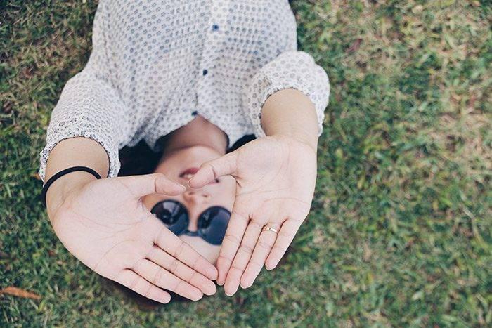 Kvinna som visar ett hjärta med sina händer
