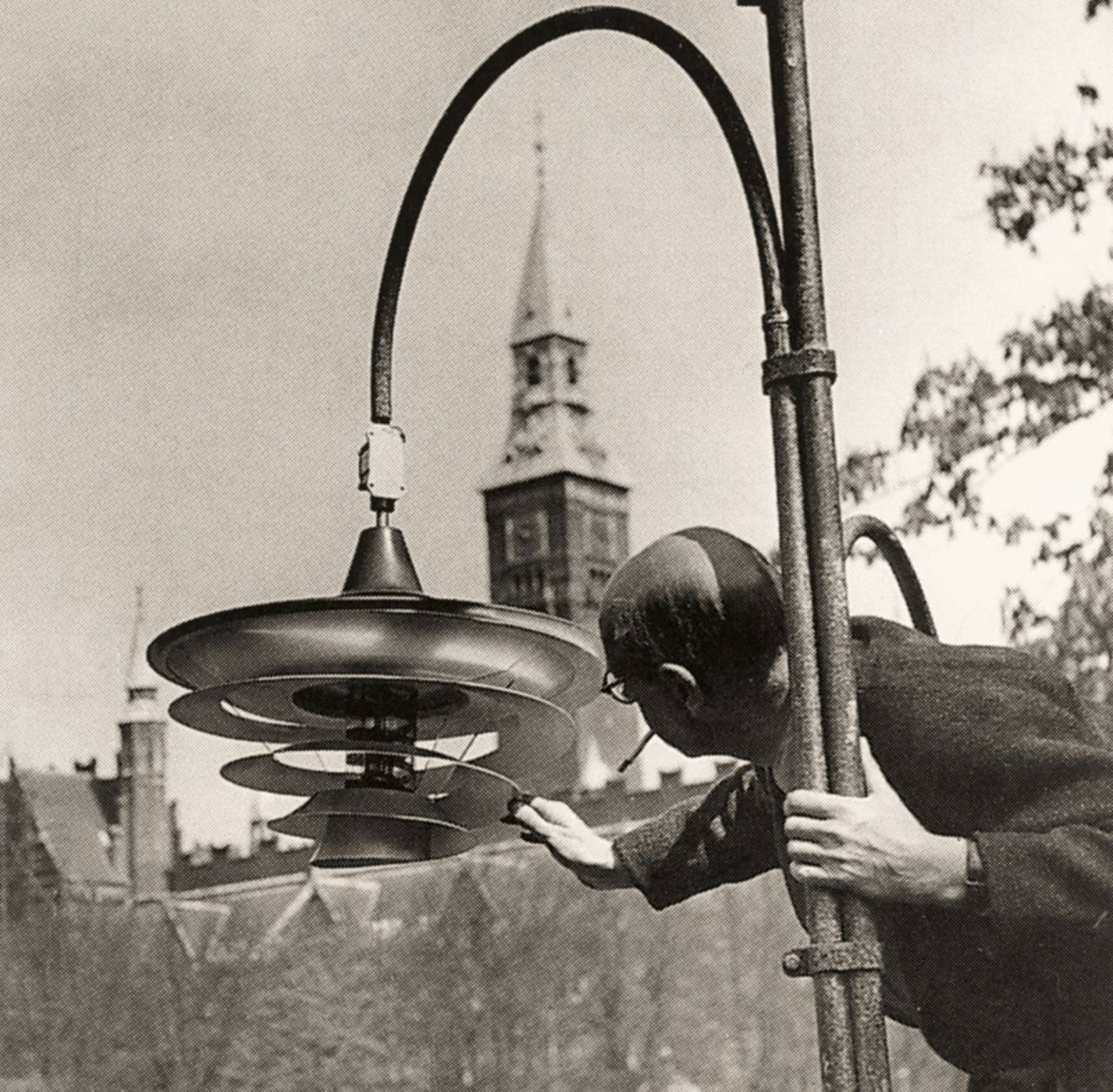 Poul Henningsen tänder en av sina lampor i nöjesparken Tivoli