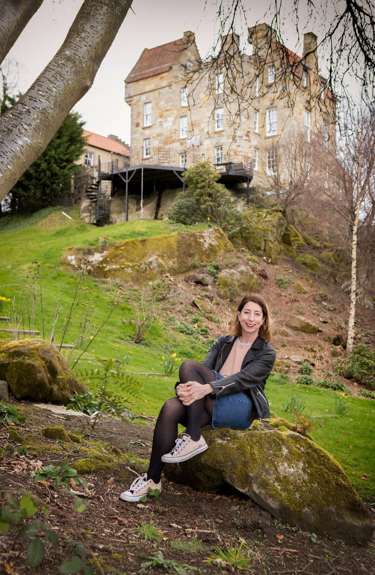 Författaren Jenny Colgan sitter framför ett slott i Skottland där hon bor med sin familj.