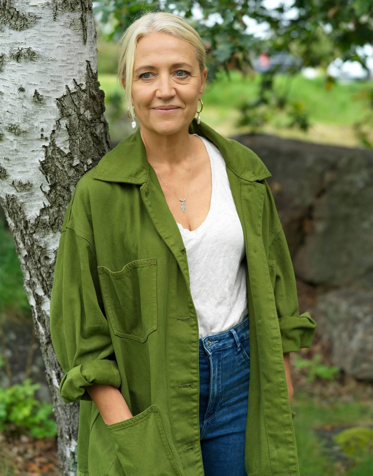 Skådespelaren Klara Zimmergren står i grön skjorta vid en björk.