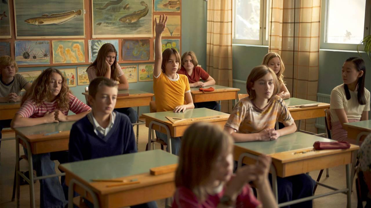 Bild från ett klassrum ur filmen En komikers uppväxt, huvudkaraktären Juha räcker upp handen.