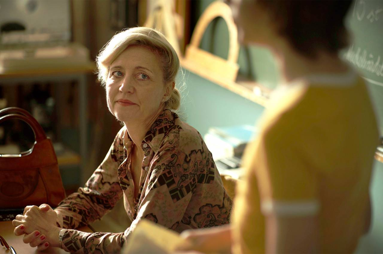 Skådespelaren Klara Zimmergren som lärare vid en kateder i filmen En komikers uppväxt.