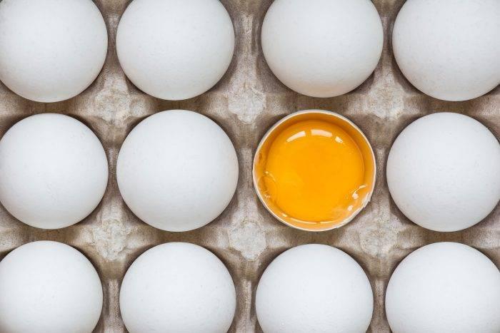 Ett knäckt ägg bland hela ägg i en äggkartong.
