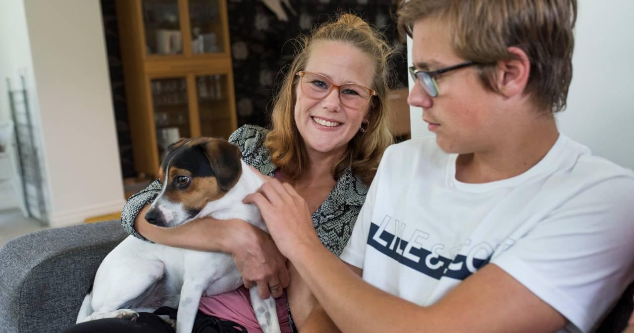 Lisa och sonen Rasmus sitter i soffan, pratar om mobbning och gosar med familjens hund.