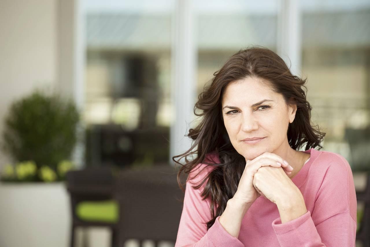 Kvinna sitter vid ett bord och ser bekymrad ut