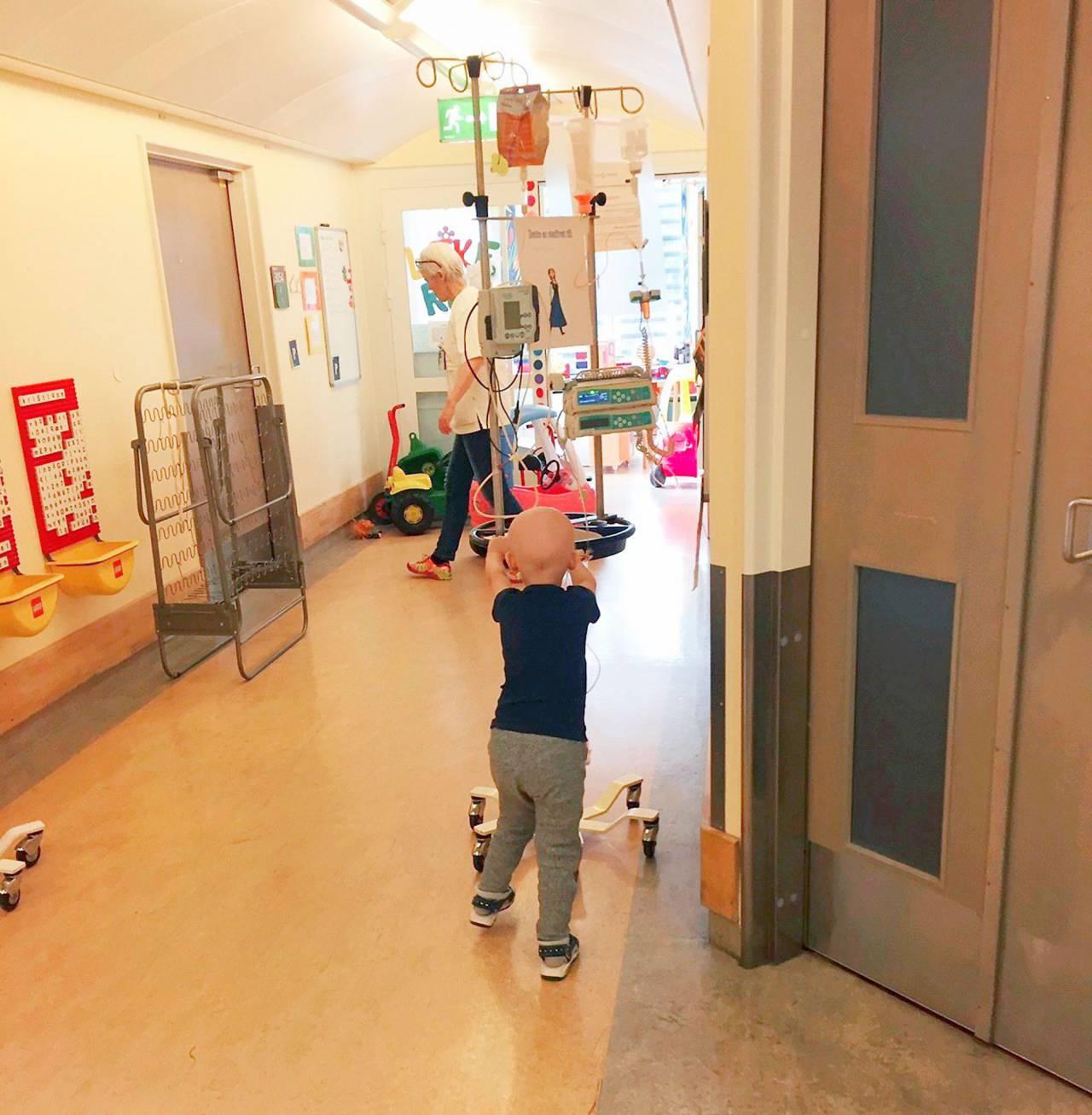 Madelene busar i sjukhuskorridoren trots att hon mår dåligt.