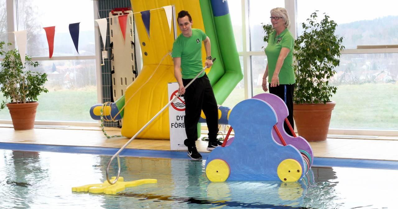Anna-Karin och Oscar som både jobbar som badvakter kontrollerar en pool på ett badhus.