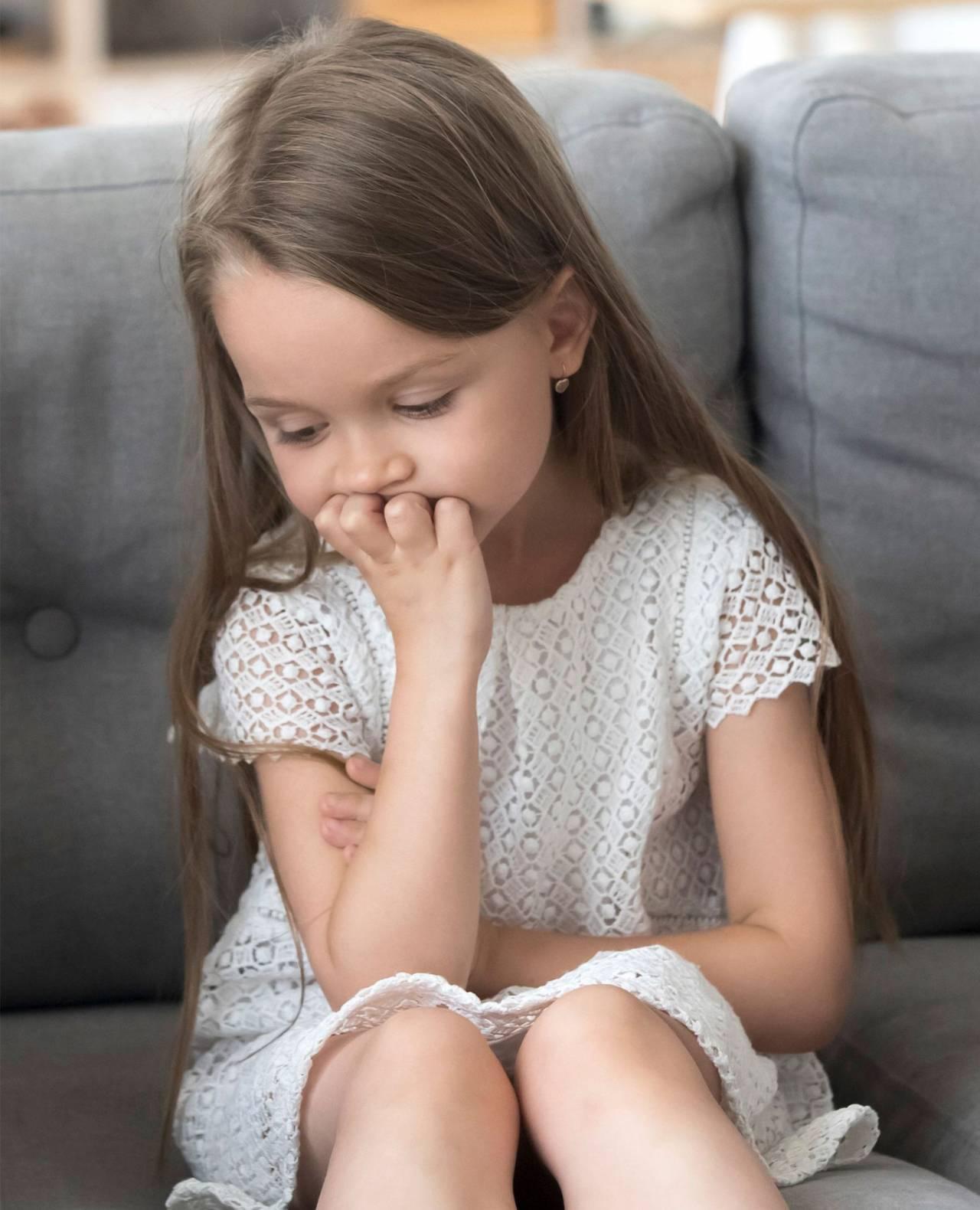 En liten flicka sitter på en soffa och ser ledsen ut.