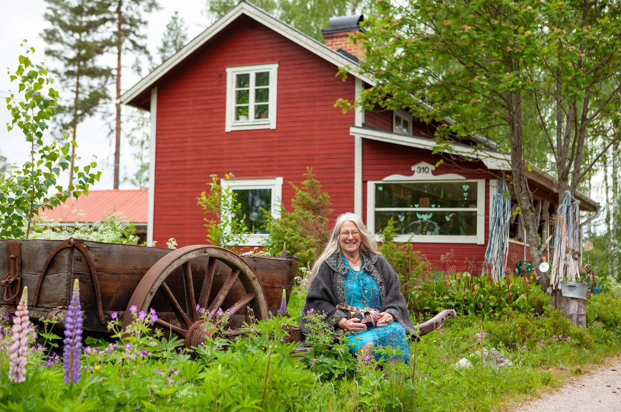 Sacha, en äldre kvinna i långt grått hår, sitter i grönskan framför ett rött hus.