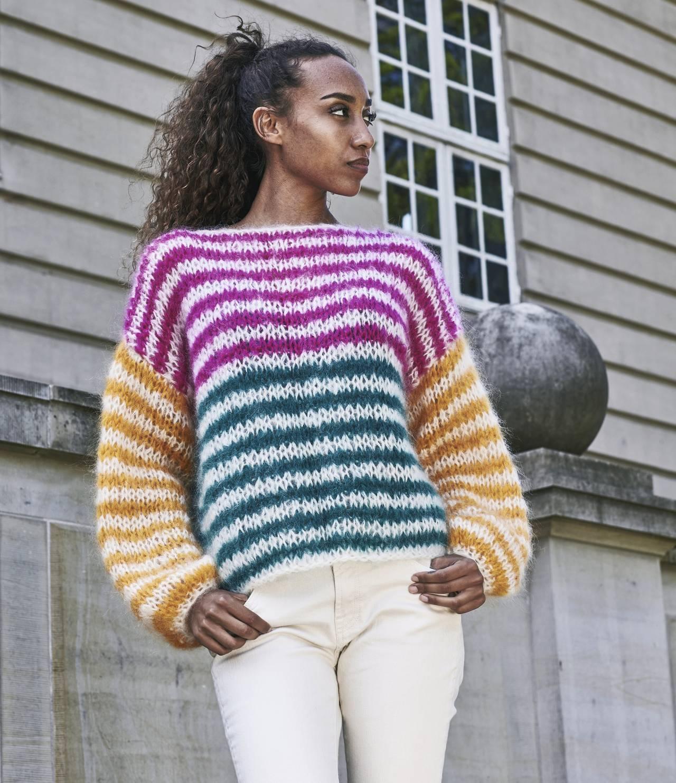Ung kvinna i klädd hemstickad tröja med färgglada ränder