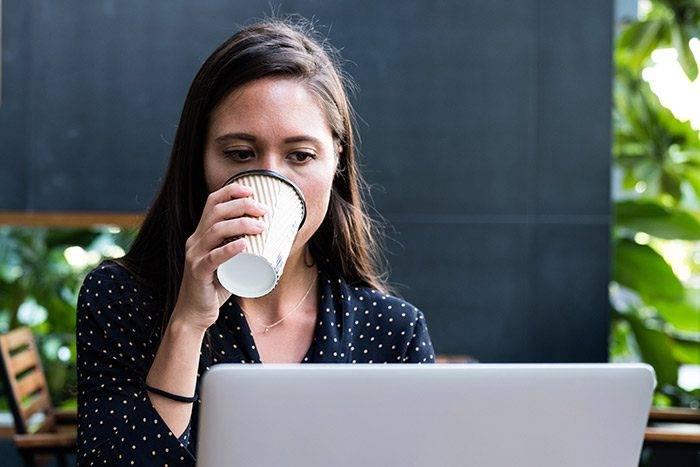 tjej dricker ur en kopp, sitter framför en dator och ser koncentrerad ut