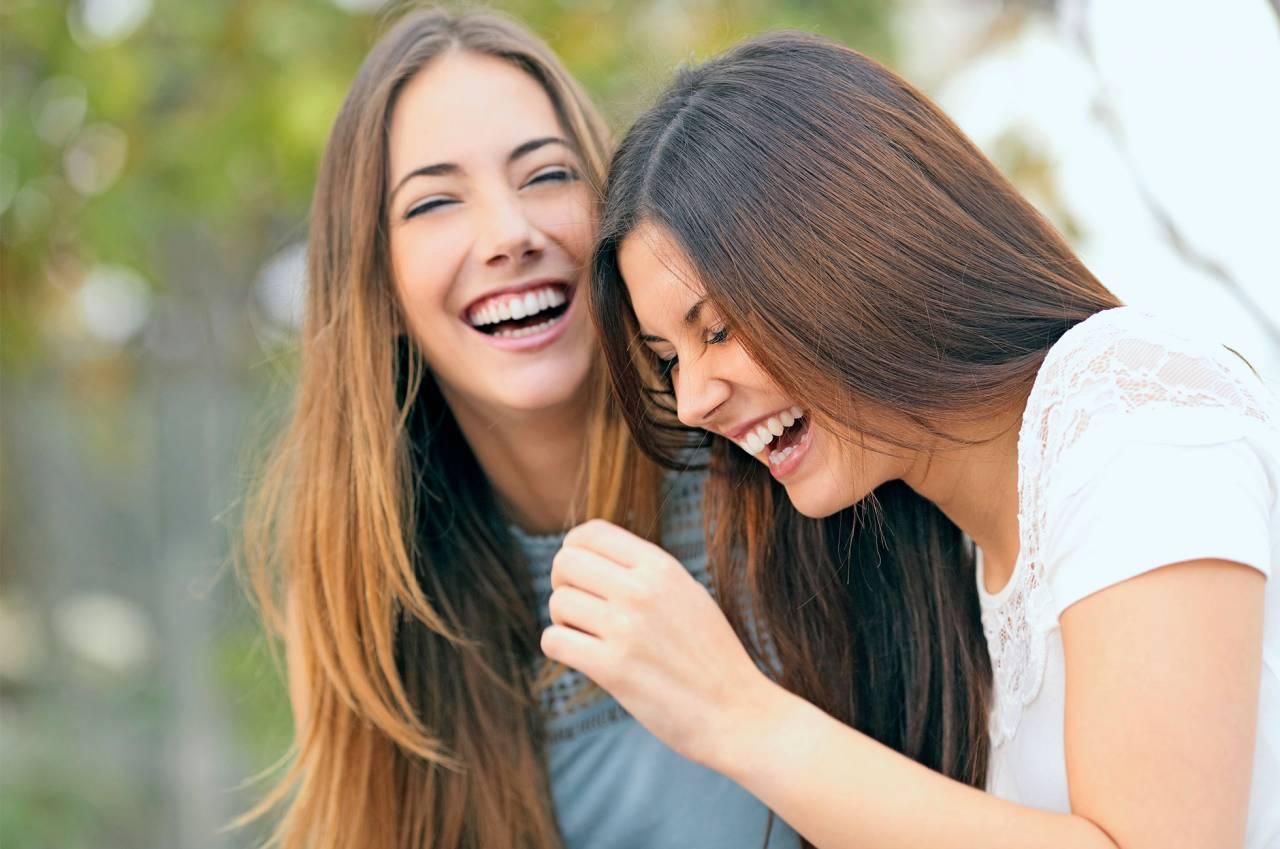 Två unga kvinnor skrattar jättemycket.