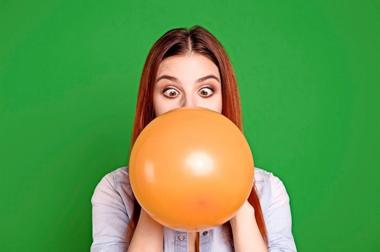 En ung kvinna blåser upp en ballong och har ögonen i kors.