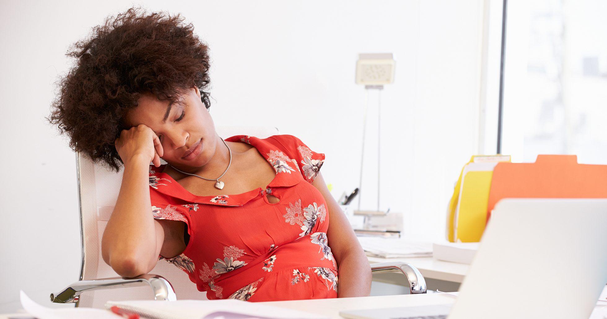 Trött kvinna vid skrivbord
