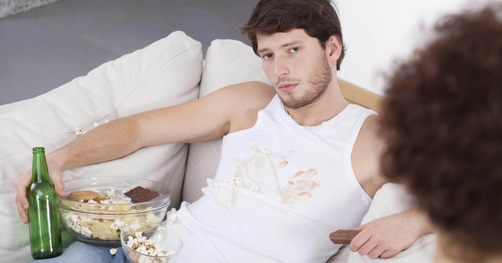 Ung man halvligger i en soffa