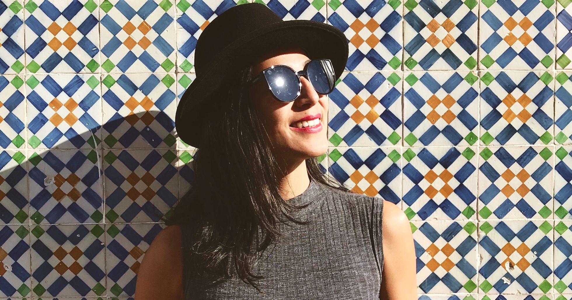 Kvinna i hatt och solglasögon ler