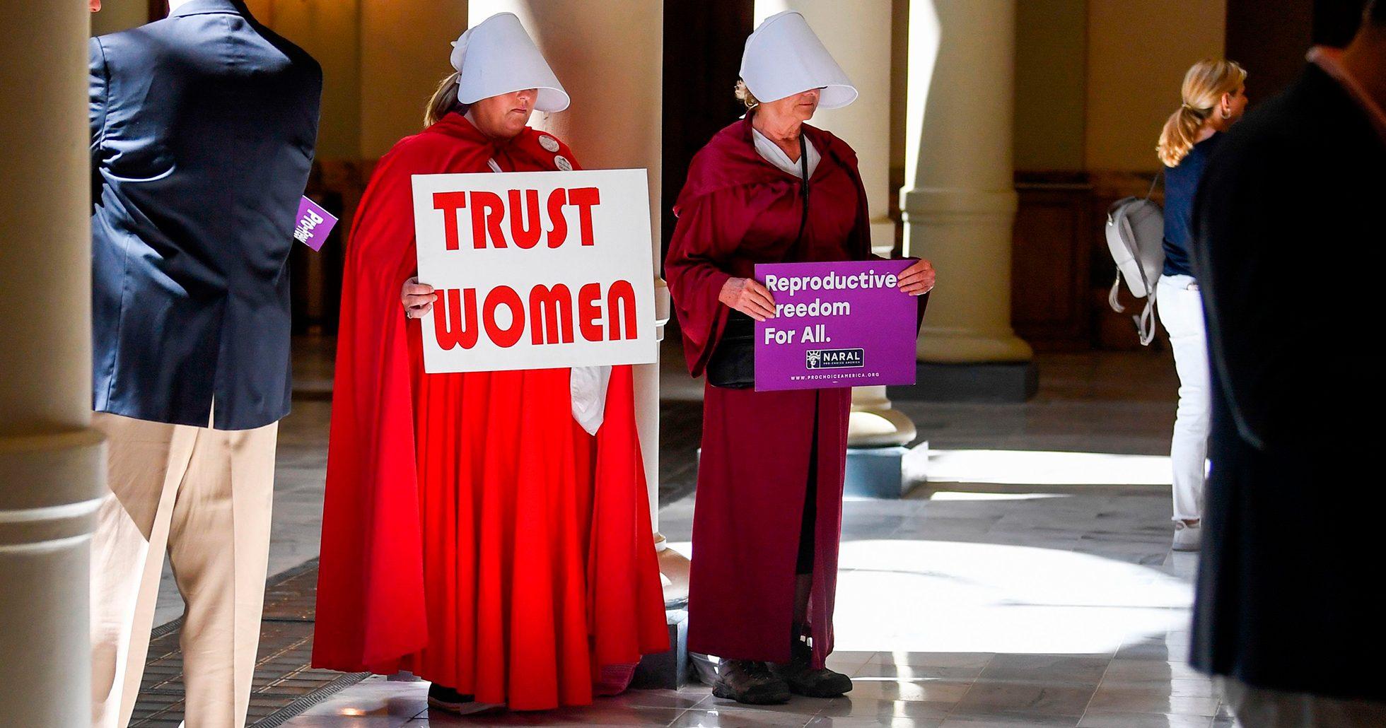 Kvinnor, klädda som karaktärer i handmaid's tale, protesterar mot Alabamas stränga abortlag.