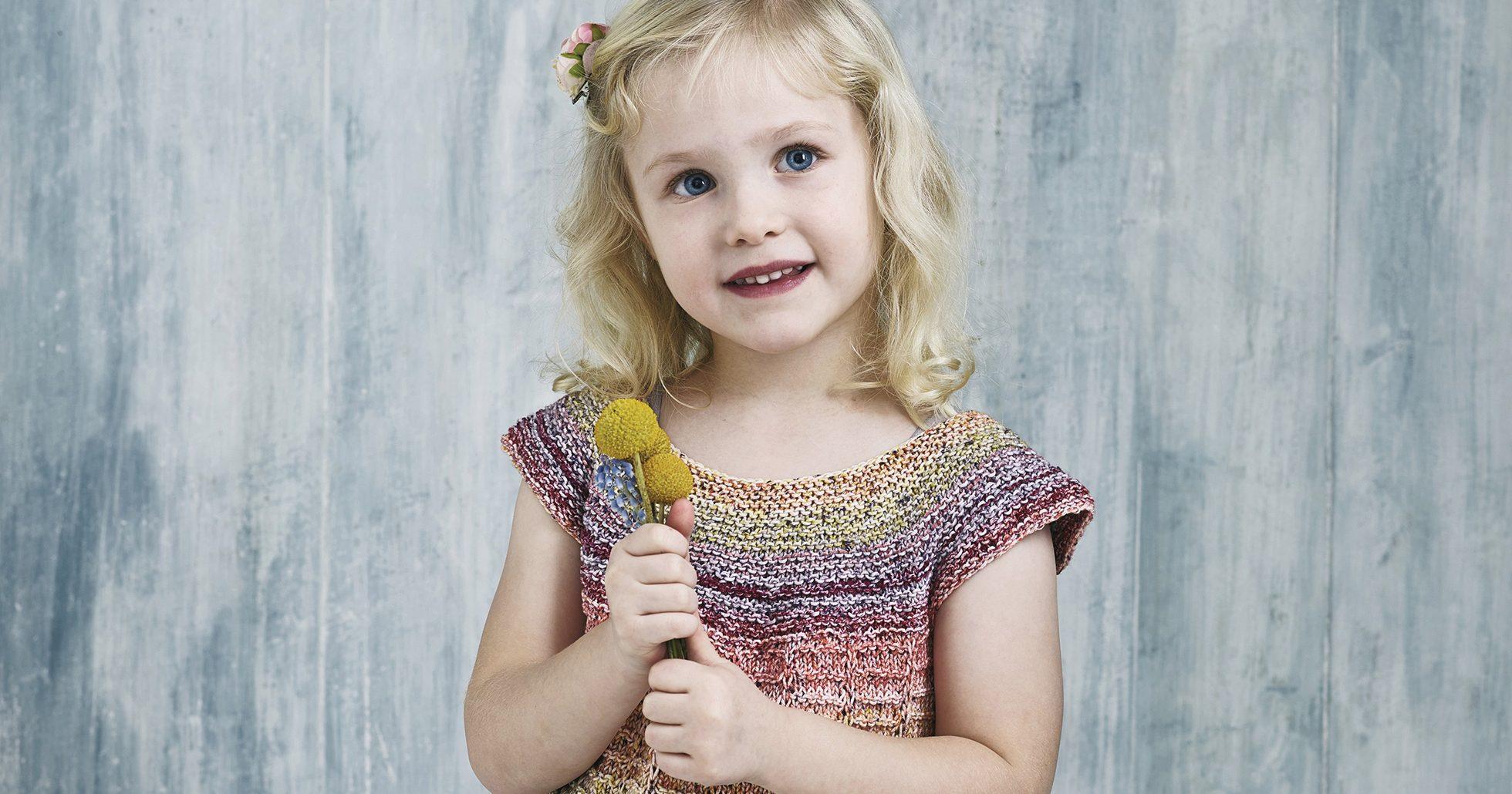 Flicka i söt stickad tröja håller blomma