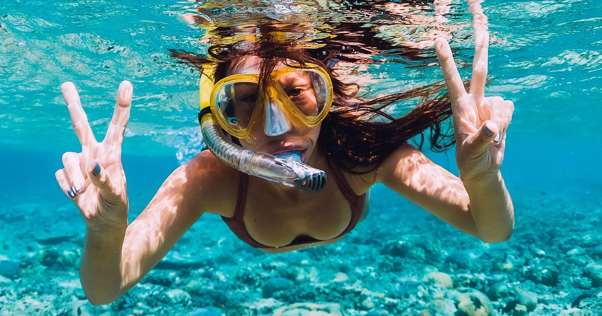 Kvinna simmar under vattenytan med cyklop