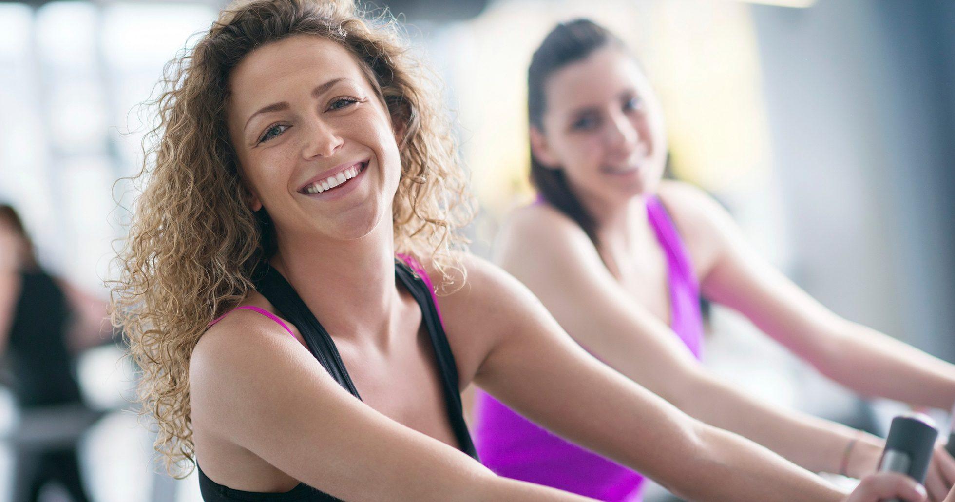 Kvinnor på gymmet ler mot kameran