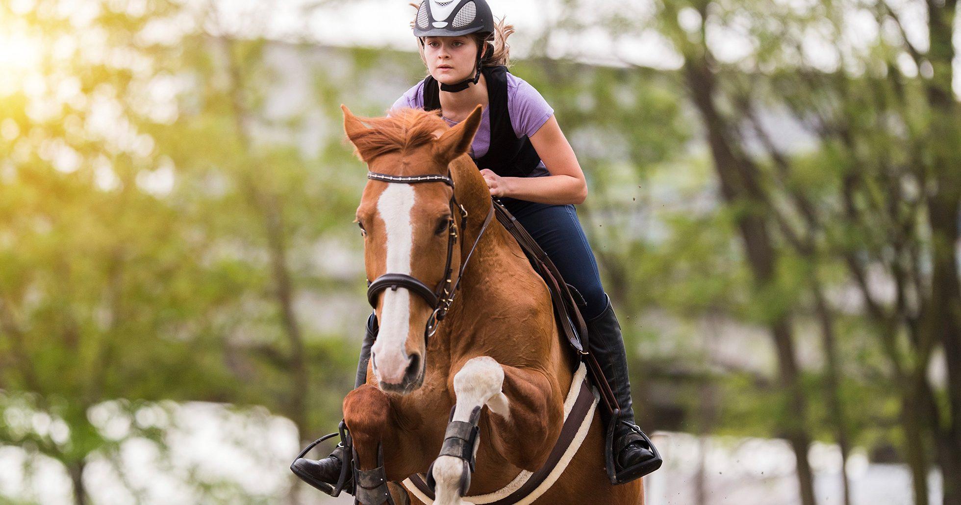 Ung tjej på hästryggen