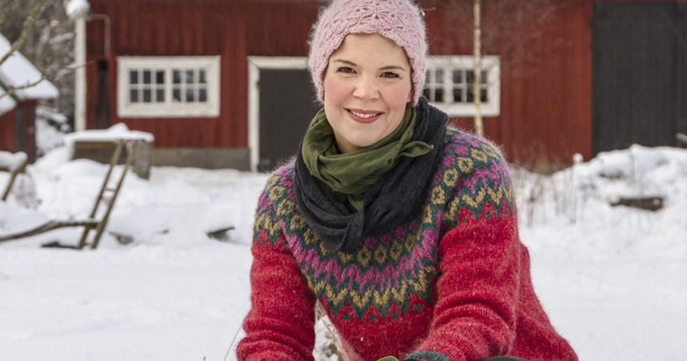 Sara Bäckmo I vinterlandskap framför rött hus.
