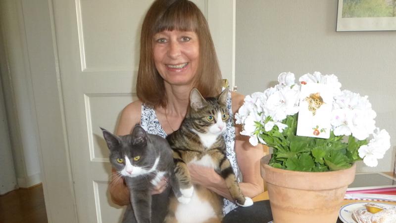 Matte med två katter i famnen